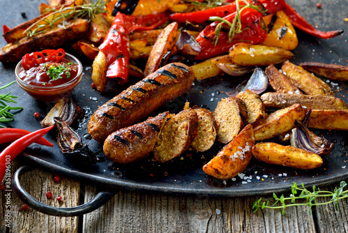 Fototapeta Vegane Bratwust vom Grill mit scharfer Sauce und Potato Wedges  - Grilled vegan sausages with hot sauce and vegetables obraz