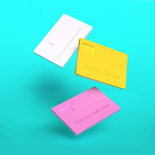 Creative Concept Of Three Colorful Plastic Credit Card In White, Yellow And Pink Colors Flying In The Air. 3D Rendering.