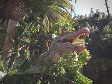 Low Angle View Of Dinosaur Statue By Trees At Universal Studios