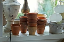 A Row Of Brown Clay Pots And G...