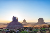 Panoramic view of merrick mitten buttes and horizon in Monument Valley at sunrise colorful light and sun beam rays behind rocks in Arizona