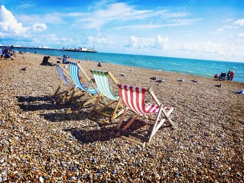 Fényképezés Colorful Deck Chairs At Pebbles Beach Against Sky On Sunny Day