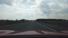 Red Sports Car Driving Down Empty Highway On Overcast Day Then Driving Past Random Object On Highway