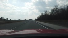 Red Sports Car Hood Driving Down Empty Highway With Very Little Oncoming Traffic
