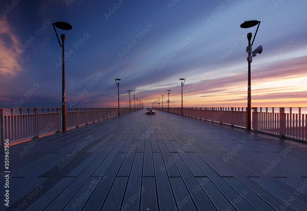 Fototapeta Molo w Kołobrzegu,wschód słońca na wybrzeżu Morza Bałtyckiego.