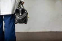 Female Physician Holding A Black Leather Doctor's Bag Heading To The Office To Practice Medicine