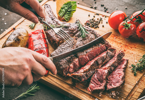 Obraz Hands cut grilled tomahawk meat medium rare or rib eye steak on wooden cutting board with grilled vegetables on dark background, close up, toning - fototapety do salonu