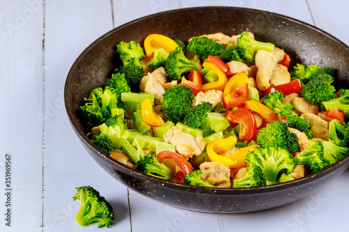 Photo Tasty healthy stir fry vegetables with chicken in pan on white surface
