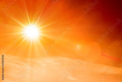 Fototapeta Orange sky with bright sun symbolizing climate change and global warming obraz