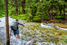 Man Crossing Fording River On Conundrum Creek Trail In Aspen, Colorado In 2019 Summer In Forest Woods With Strong Current And Deep Water