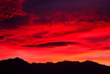 Silhouette Mountains Against Cloudy Red Sky During Sunset