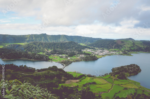 Fototapety, obrazy: Amazing view of the Lagoa Azul and village Sete Cidades from the Miradouro do Cerrado das Freiras viewpoint in Azores, Portugal. Lakes surrounded by green fields and forest. Horizontal photo.