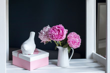 Three Red Peonies In A White Porcelain Jug On A Black Background, A Pink And White Box With A Heart With A Gift And An Earthenware Figurine Of A Bullfinch Bird.