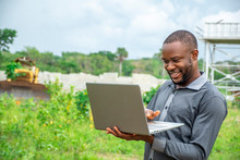 Young African Agricultural Businessman, Using A Laptop On A Plot Of Land