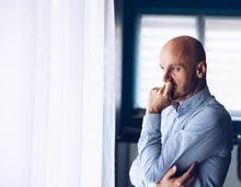 Worried Businessman In Office. Thoughtful Man Looking Through The Window.