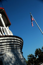 Low Angle View Of American Flag And Building Against Clear Blue Sky