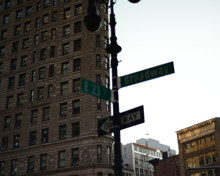 Low Angle View Of Road Sign Against Flatiron Building In Manhattan