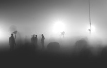 Silhouette People Standing On Illuminated Field In Foggy Weather