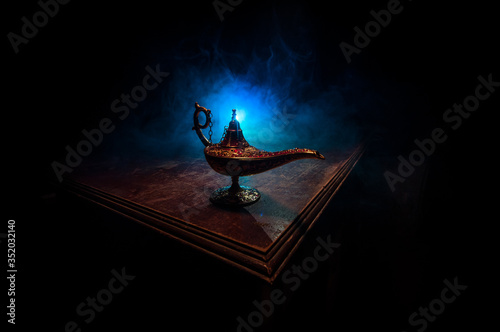 Lamp of wishes concept. Antique Aladdin arabian nights genie style oil lamp with soft light white smoke, Dark background.