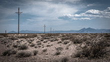 Scenic View Of Utility Poles On A Wide Arid Land