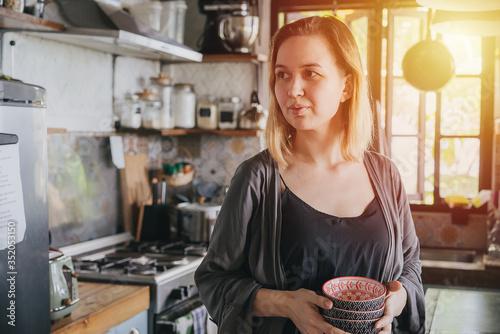 Fotografering Portrait of sensual emotionless mature woman in sun-lit kitchen