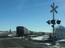 Railroad Crossing Sign By Road Against Sky