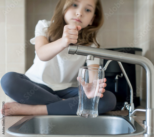 Fényképezés Child is holding an empty glass nearby a stainless steel kitchen tap