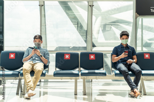 Obraz Social distancing, two men wearing face mask sitting keeping distance away from each other to prevent covid19 infection during pandemic. Empty chair seat red cross shows avoidance in airport terminal. - fototapety do salonu