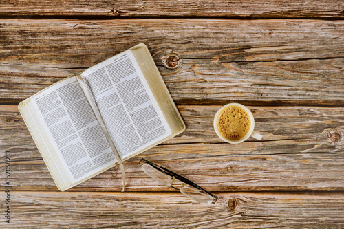 Obraz Open Bible morning readings on a table top with coffee cup and eyeglasses - fototapety do salonu
