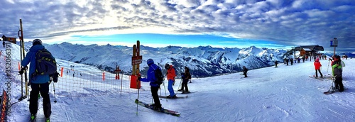 Foto Panoramic View Of People Skiing On Snowcapped Mountain Against Cloudy Sky