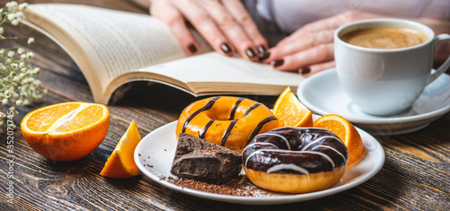 Woman is reading a book and having breakfast. Meal consists of cup of natural black coffee with fresh orange, donuts with orange and chocolate. Bright summer Breakfast, a tasty start to the morning