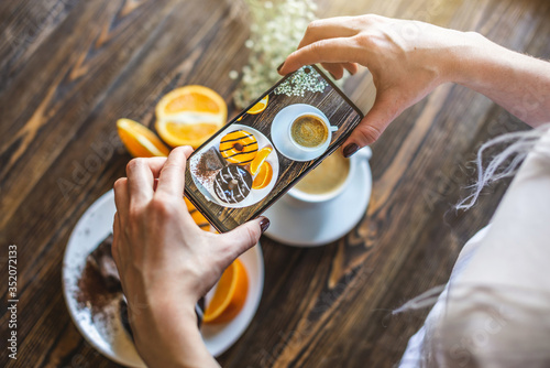 Woman is take photos her appetizing bright breakfast using a phone. Meal consists of a Cup of natural black coffee with fresh orange, donuts with orange and chocolate. Top vew