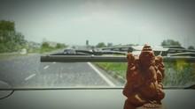 Close-up Of Ganesha Idol On Car Dashboard Against Sky