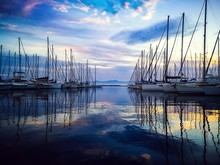 Sailboats Moored On Harbor Against Sky During Sunset