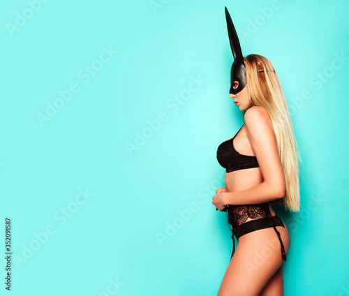 Fototapeta Portrait of young beautiful sexy woman with large breasts. Model wearing carnival black mask of Easter bunny rabbit.Hot blonde girl posing near blue wall in studio obraz