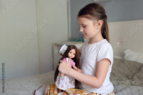 Photo Caucasian girl combing a doll with long hair, a girl playing dolls