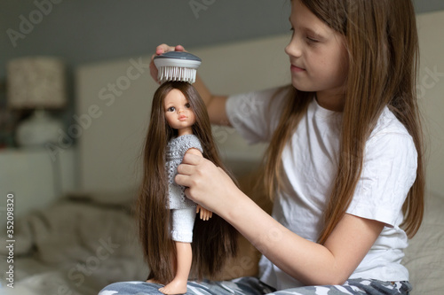 Fotografie, Obraz Caucasian girl combing a doll with long hair, a girl playing dolls