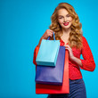 canvas print picture Happy young woman holds bags with a purchases. Beautiful trendy girl with a colorful shopping bags. Model in a red shirt over blue background holding bags with gifts. Happy caucasian woman.