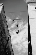 Low Angle View Of Shoes Hanging At Wire Against Sky