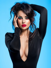 Portrait Of Beautiful Young Woman With Bright Blue Makeup.  Pretty Girl With Long Black Hair. Brunette Woman In A Black Clothes. Sexy Girl. Beautiful Brunette With Bright Red Lipstick On Her Lips..