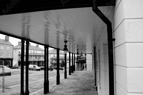 Canvas Print Colonnade Against Cars On Road And Buildings