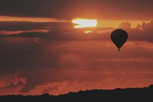 Silhouette Hot Air Balloon Against Cloudy Sky During Sunset