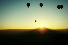 Silhouette Hot Air Balloons Over Landscape Against Clear Sky During Sunset