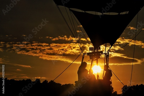 Fotografiet Low Angle View Of Silhouette People At Hot Air Balloon Against Sky During Sunset