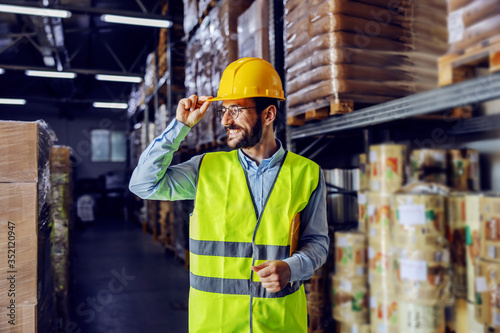 Photo Young smiling supervisor in vest, helmet on head and folder under armpit going around warehouse and checking on inventory