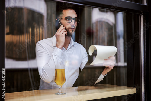 Obraz na plátně Young serious businessman in shirt sitting in pub after work, holding paperwork and calling boss after work