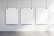 Three Vertical Mock Up Posters On White Wall