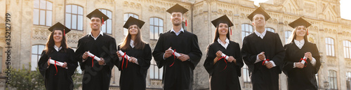 Photo Happy students with diplomas near campus. Banner design