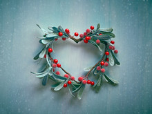 Decorative Christmas Heart Shaped Wreath With Frosted Mistletoe Leaves And Red Berries Hanging On A Light Textured Wooden Door