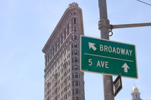 Low Angle View Of Sign Board On Pole By Flatiron Building Against Sky